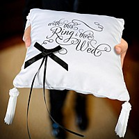 Closeup of ring bearer holding With This Ring I Thee Wed Ring Pillow