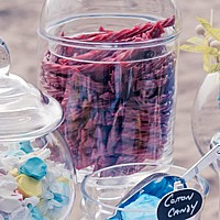 Straight sided clear glass apothecary jar filled with red licorice