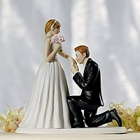 Cake topper with groom on one knee kissing brides hand