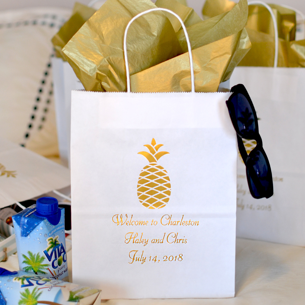White 8 x 10 Kraft paper wedding welcome bag custom printed with WD100A Pineapple design and three lines of custom print with Florentine Cursive letter style in Metallic Gold imprint color