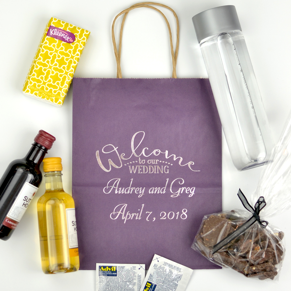 Purple kraft paper gift bags personalized with Arched Welcome design, bride & groom's names, and wedding date in Florentine Cursive letter style in Platinum Satin imprint color and showcasing ideas for bag contents