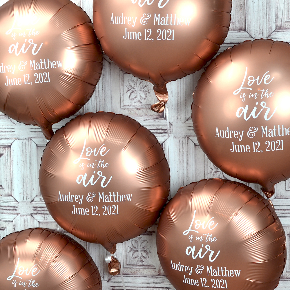 Round foil balloons custom printed with W0035 Love is in the Air design, bride and groom names, and date in White imprint using Sweetheart lettering style