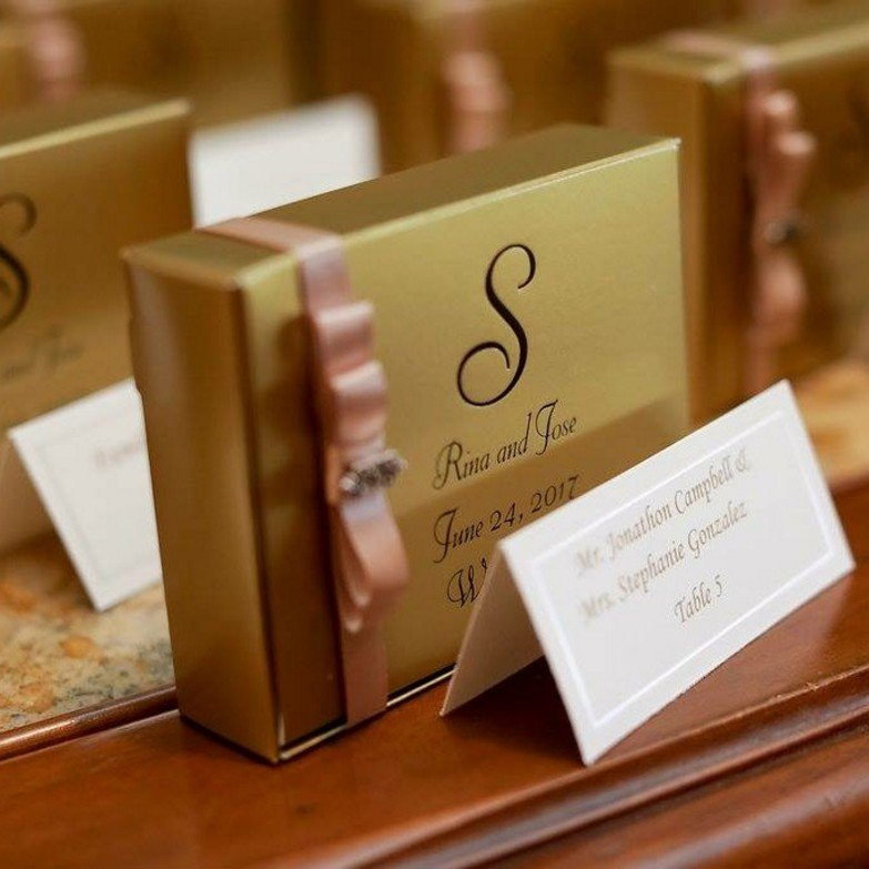 Gold personalized wedding cake favor boxes decorated with ribbon on table