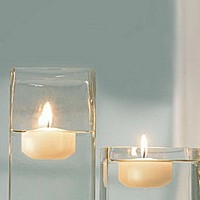 Ivory floating candles in square vased filled with water and rocks