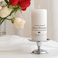Personalized white memorial candle banded with metallic silver ribbon and silver plated pedestal stand
