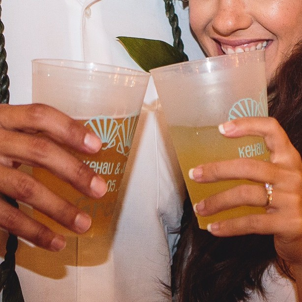 Bride and groom holding personalized wedding cups