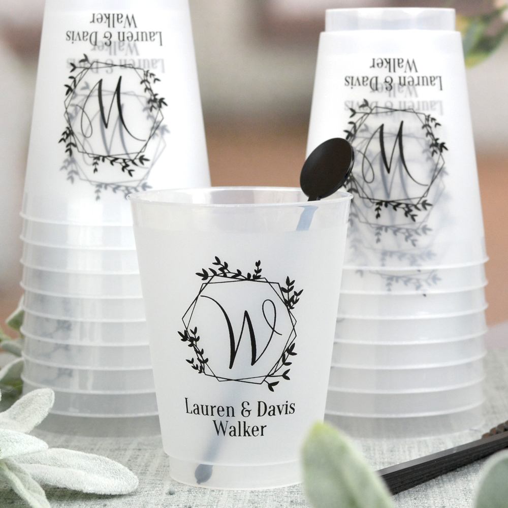 Dishwasher safe frosted clear plastic wedding cups personalized with single initial monogram geometric wreath and 2 lines of custom print in Black imprint color. See what your wedding cups will look like with free instant online proofing
