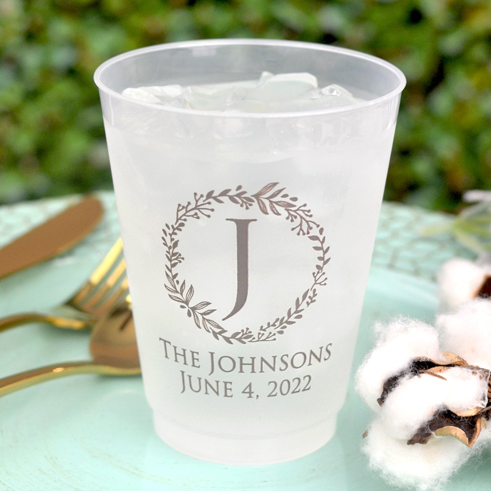 Dishwasher safe frosted clear plastic wedding cups personalized with single initial monogram wreath and 2 lines of custom print in Taupe imprint color. See what your wedding cups will look like with free instant online proofing