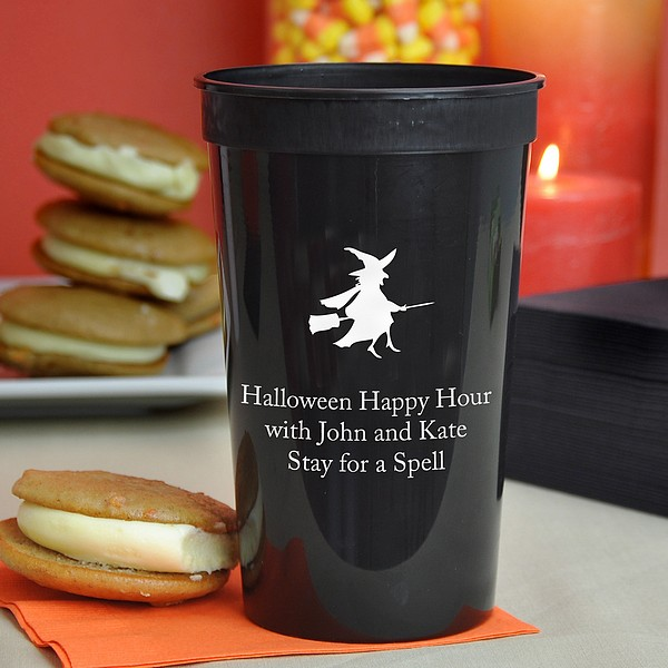 Black 22 ounce plastic stadium cup custom printed with witch and broom Halloween design and 3 lines of text in white imprint color