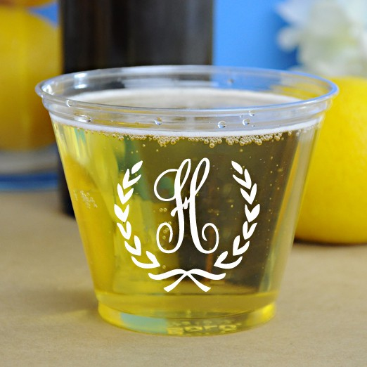 Clear personalized plastic disposable solo cups printed with White imprint color and Monogram Format B-15 using Flemish lettering style