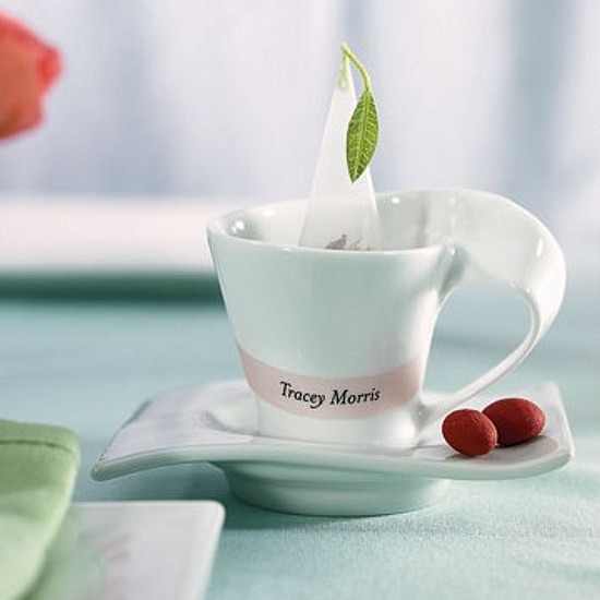 Porcelain swish cup and saucer favors shown with tea and name tag