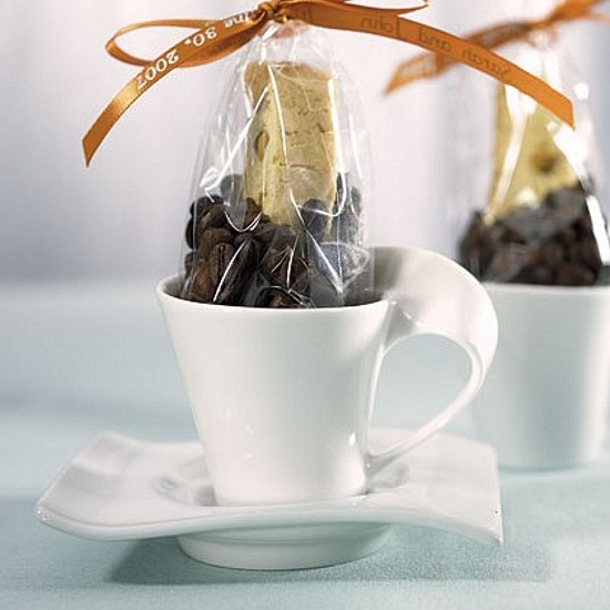 Porcelain swish cup and saucer favors shown with coffee beans and biscotti
