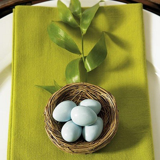 Bird nest favor with candy eggs on table place setting