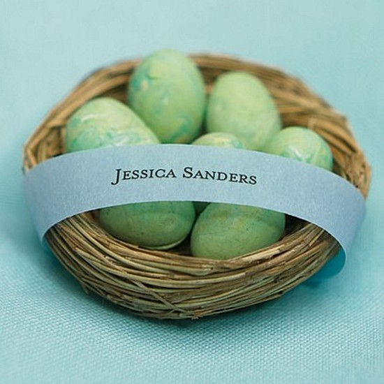Mini bird nest favor filled with foil wrapped candy eggs and wrapped with personalized ribbon