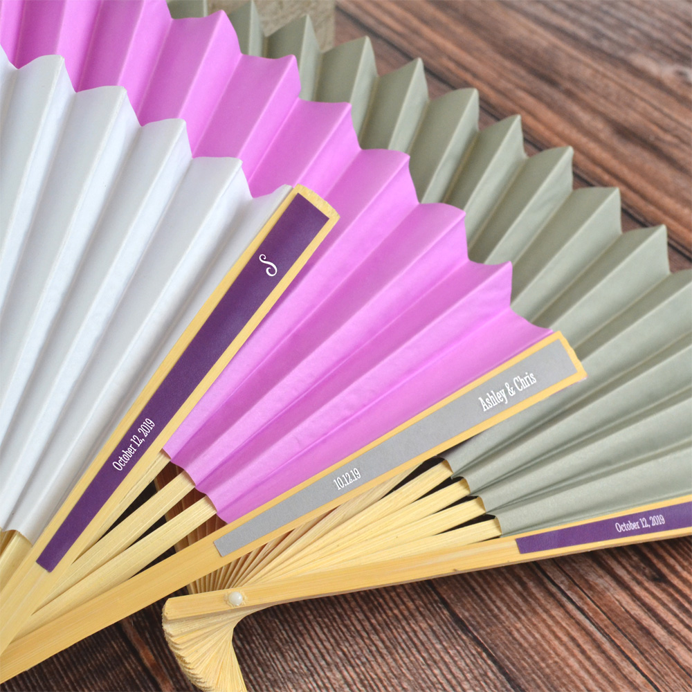 Closeup of paper accordion style hand fan with Dark Grey and Plum personalized labels with names and date and monogram and date personalization options