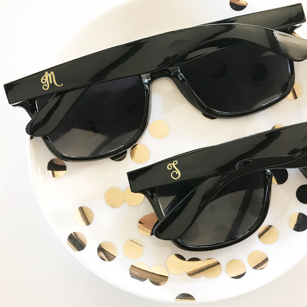Monogrammed Black & Gold Wayfarer style sunglasses are fun, on-trend gift idea for your bridesmaids and wedding guests.  Personalized with a single monogram initial in metallic gold script (on one side only). Give a pair to each of your bridemsaids or set a basket of sunglasses out at your wedding with some cute signage that says 'Don't be blinded by our love'.