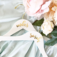 Personalized hardwood bridal party hangers are great for pairing with floral satin bridal robes as a custom bridesmaids gift or for showcasing the bride's wedding dress.