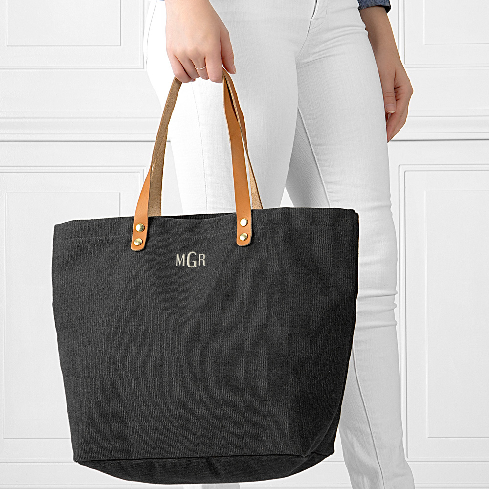 Woman shown holding black washed canvas tote bags personalized with custom embroidered 3-letter monogram