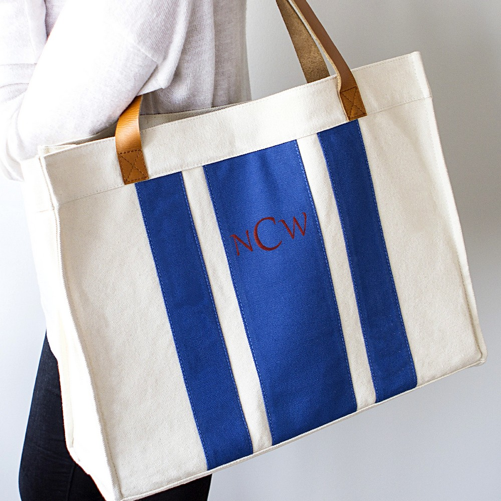 Personalized blue striped canvas tote with leather handles over woman's shoulder
