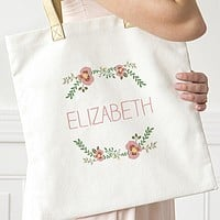 Woman carrying floral print canvas tote bag personalized with custom name