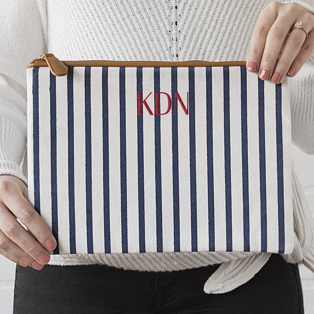 Woman holding large white and navy stripe canvas clutch personalized with 3 letter monogram