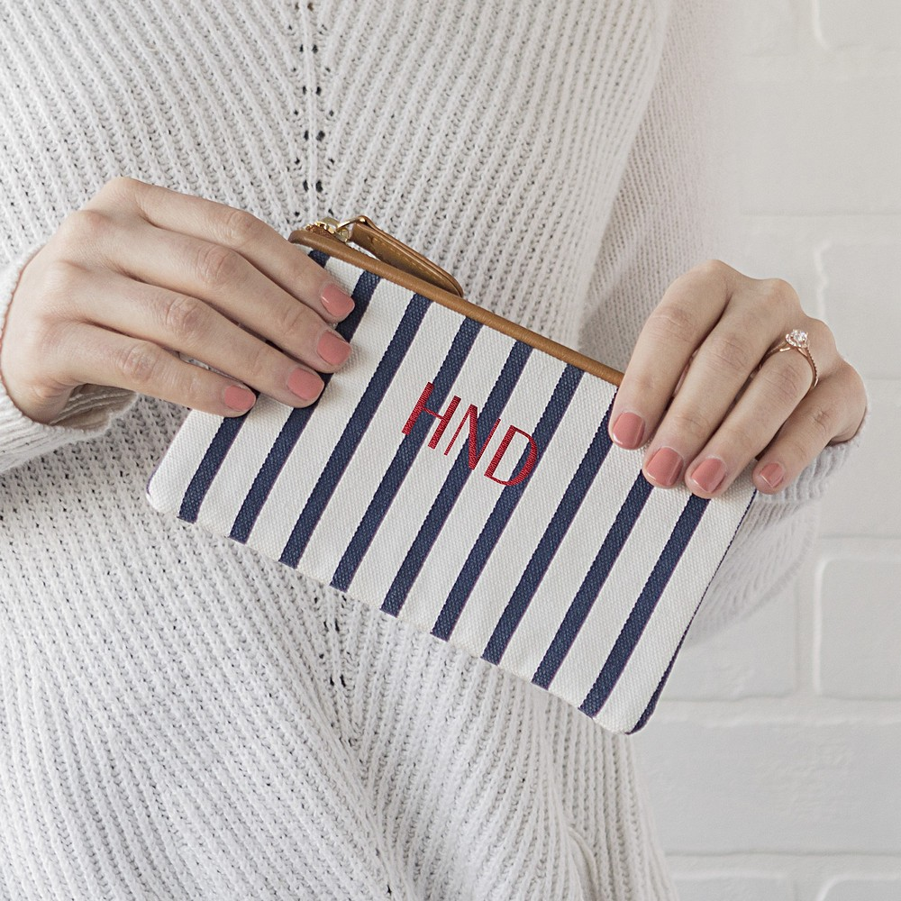 Woman holding small white and navy stripe canvas clutch personalized with 3 letter monogram