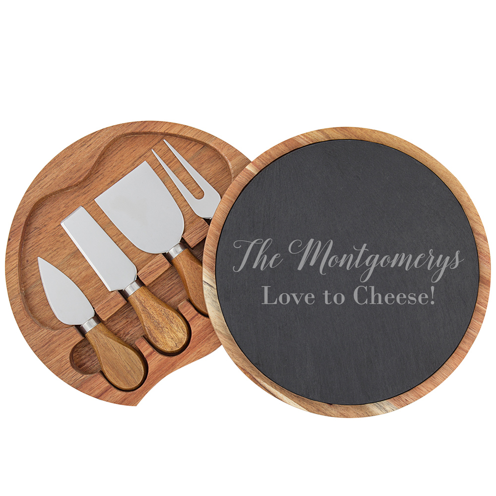 Two lines of custom text laser etched onto slate and acacia wood cheese serving board, opened to reveal included utensils