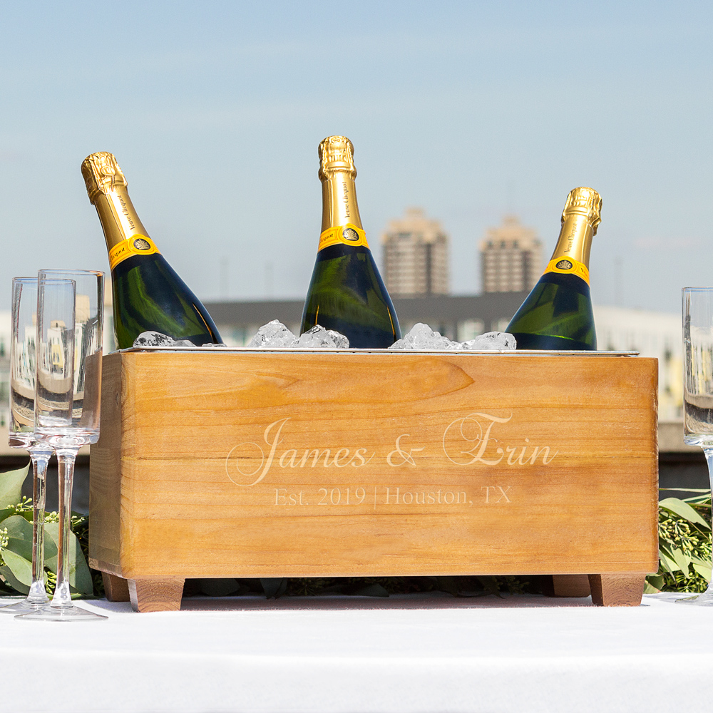Beverage chiller trough holding champagne bottles at outdoor celebration, personalized with couple's names, location, and wedding date