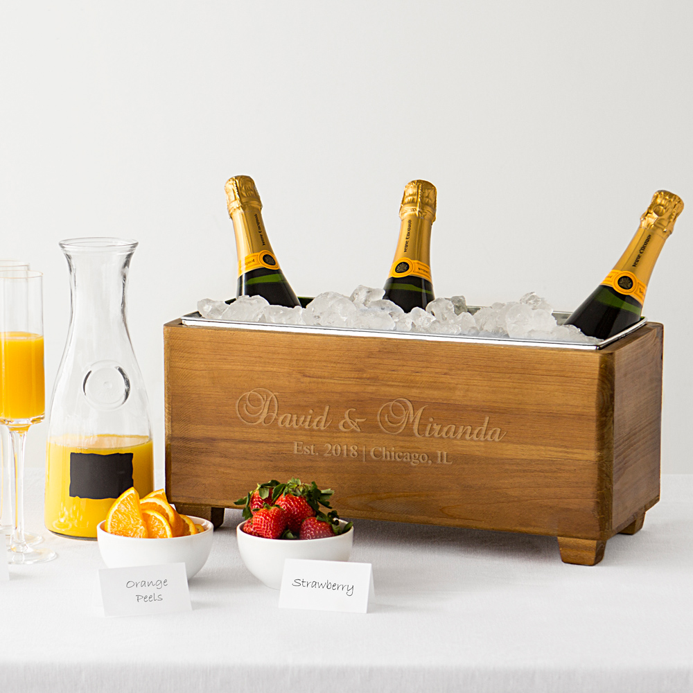 Personalized wood trough wine chiller with bride and grooms names, location, and wedding date as dinner table centerpiece holding 3 bottles of champagne