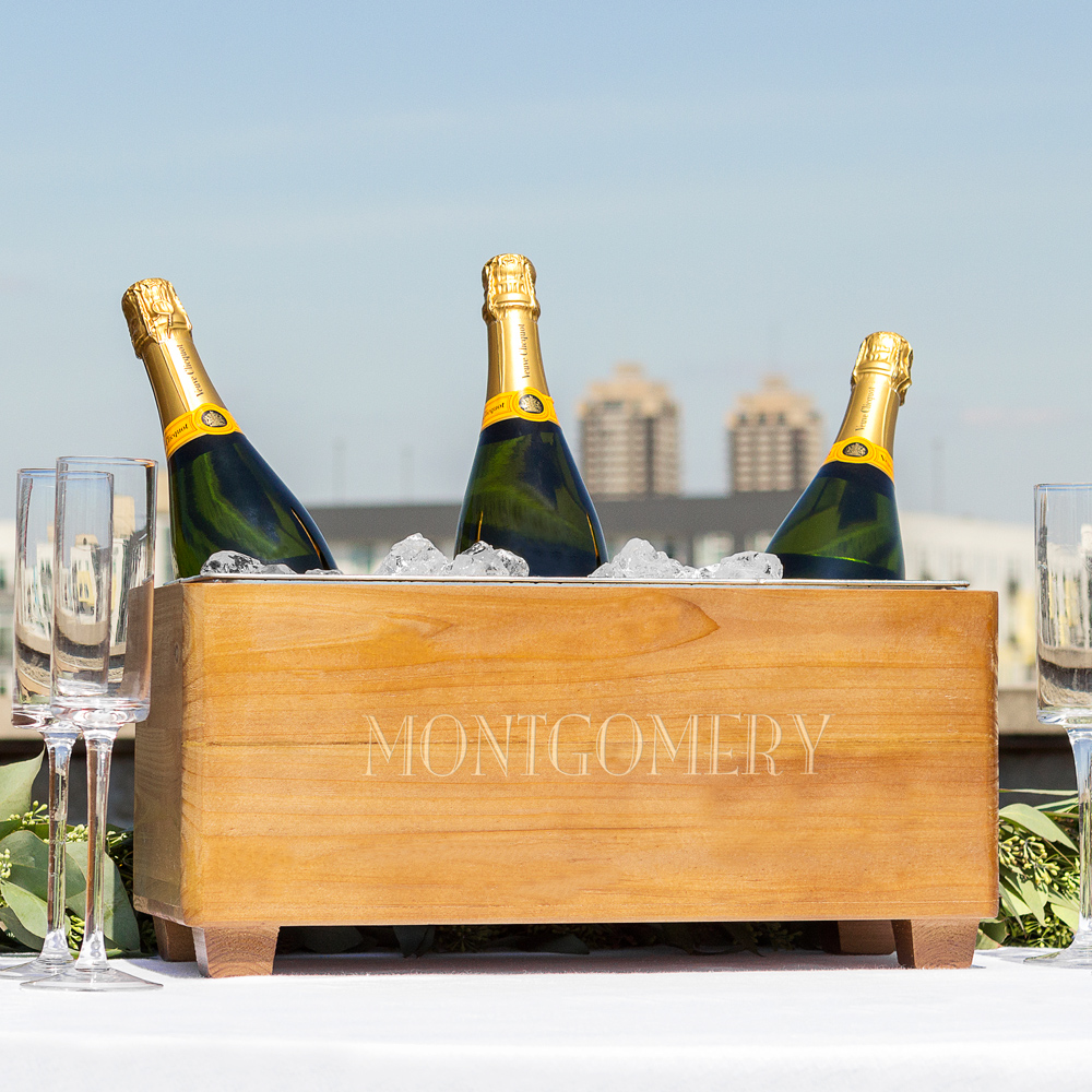 Wood trough beverage chiller engraved with family name holding champagne bottles at outdoor celebration