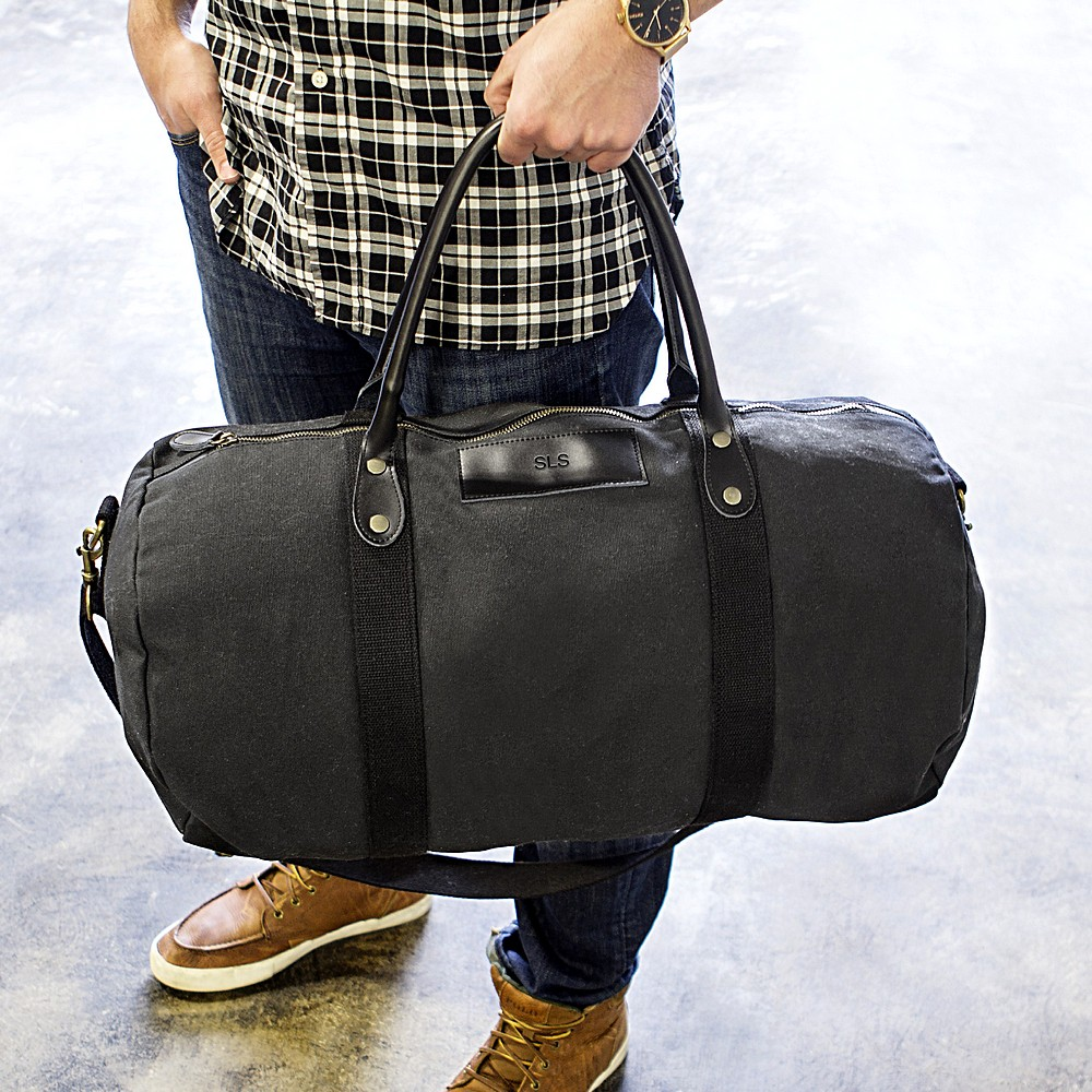 Man carrying his custom engraved black canvas and leather duffle bag