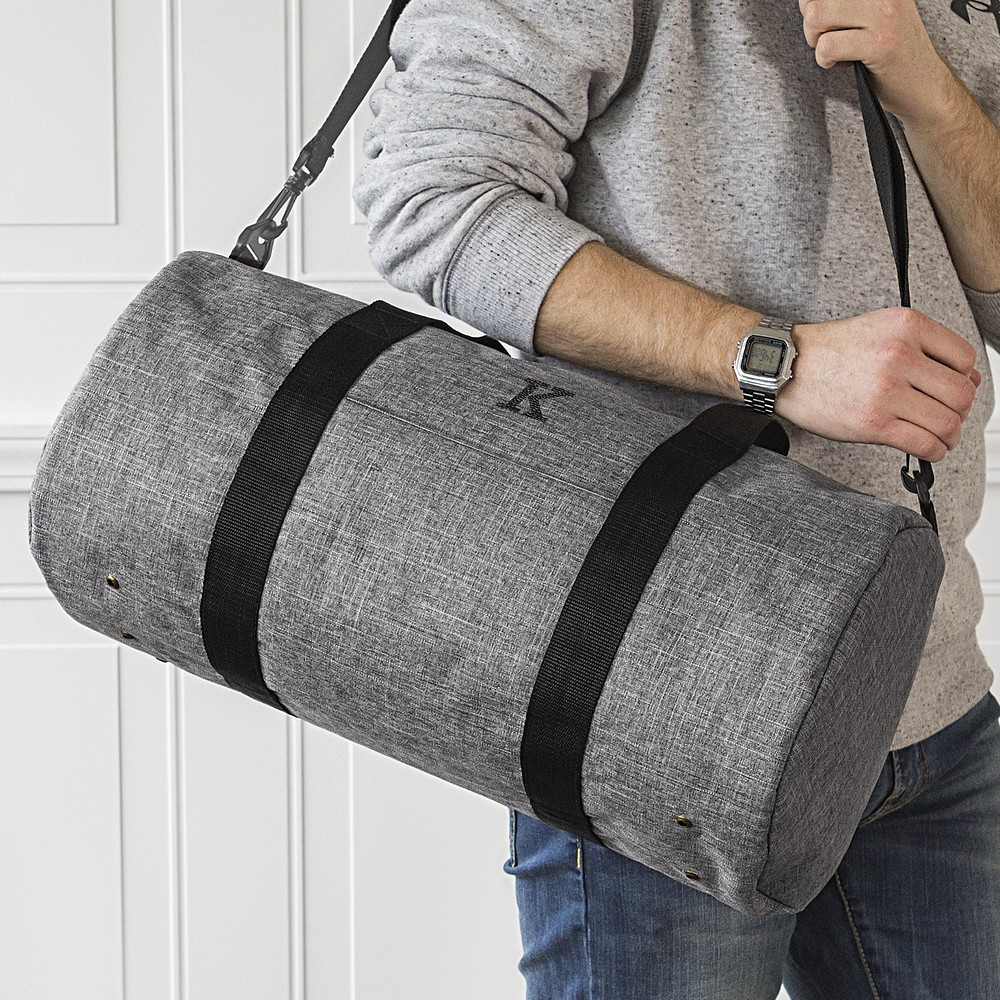 Gray crosshatch duffel bag personalized with large single initial with carry strap over man's shoulder