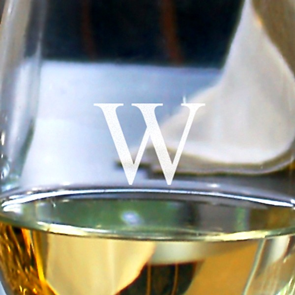 Closeup of stemless wine glass engraved with a single monogram initial