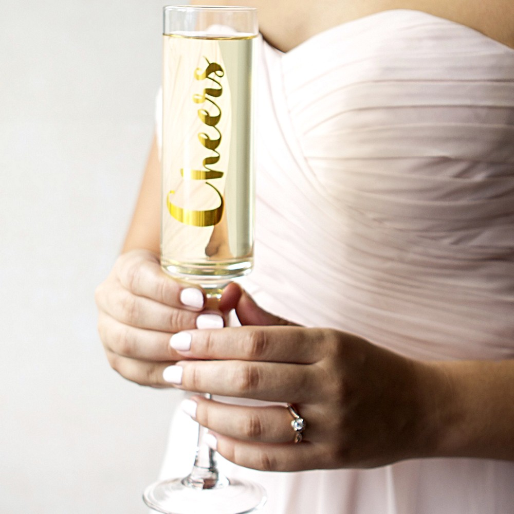 Woman holding her custom printed 8 oz. gold cheers contemporary champagne flute