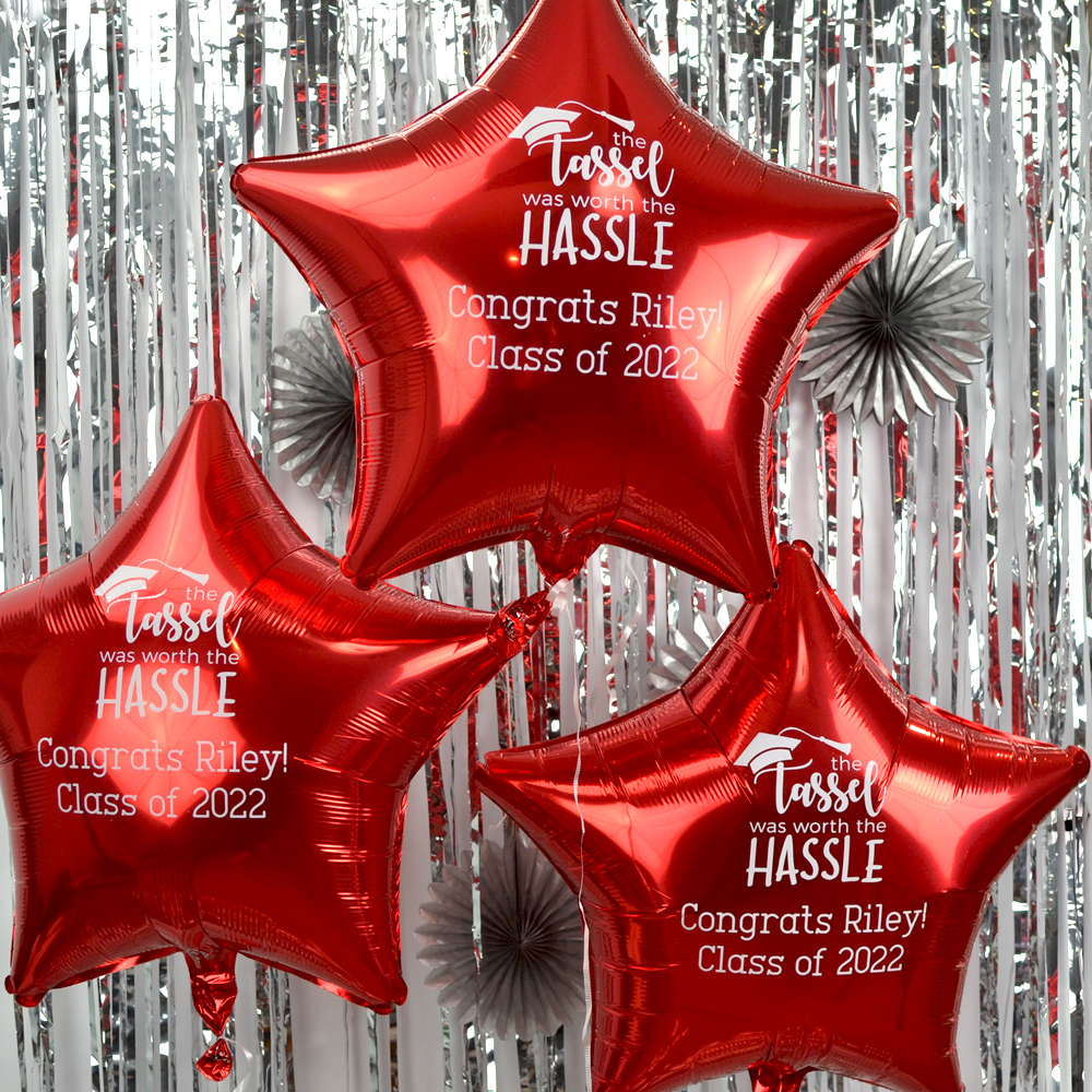 Mylar Graduation Balloon in Metallic Red with White Imprint, design G1204 - Tassle Worth Hassle and two lines of text in Adventurous Lettering Style.