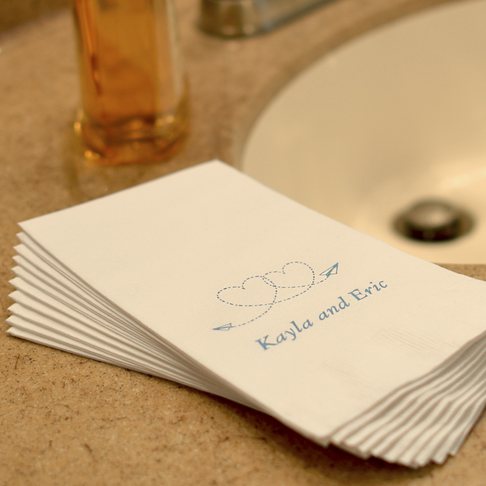 White disposable 3-ply guest hand towels with design and a line of text in Garamond Italic
