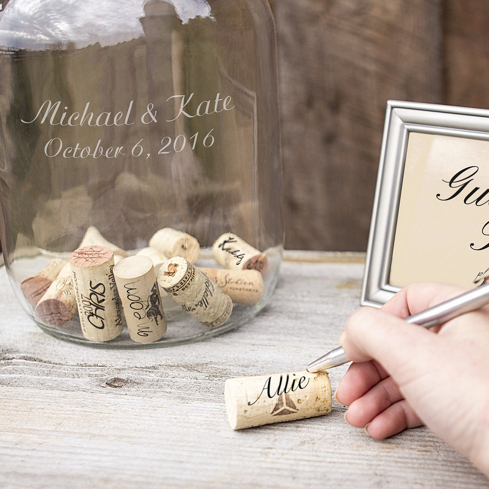 Guest signing wine cork an placing inside personalized glass gallon growler guest book alternative
