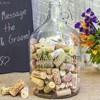 Glass gallon jug etched with bride and groom's name and wedding date, filled with guest signature wine corks