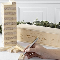 Building Memories wood block game wedding guest book piece being signed by guest