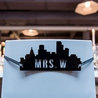 Black acrylic bride's cityscape silhouette sign on chair back