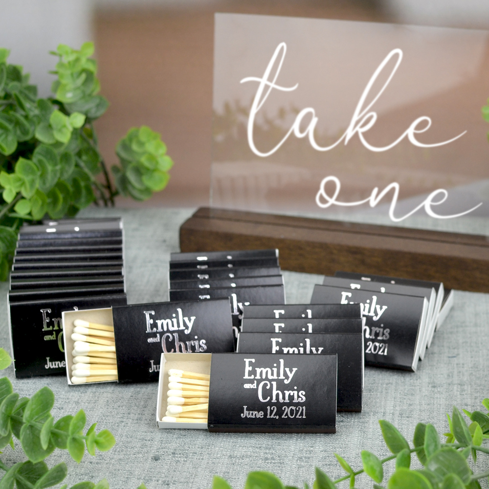 Black matchboxes personalized with monogram format M-54 and additional line of custom text using lettering style Sweetheart and imprint color Metallic Silver