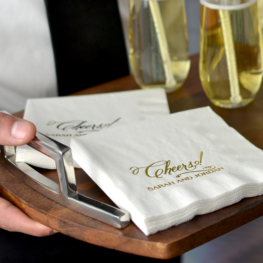 White beverage napkins with design 2227 and one line of print in Strong lettering style with Metallic Gold Imprint