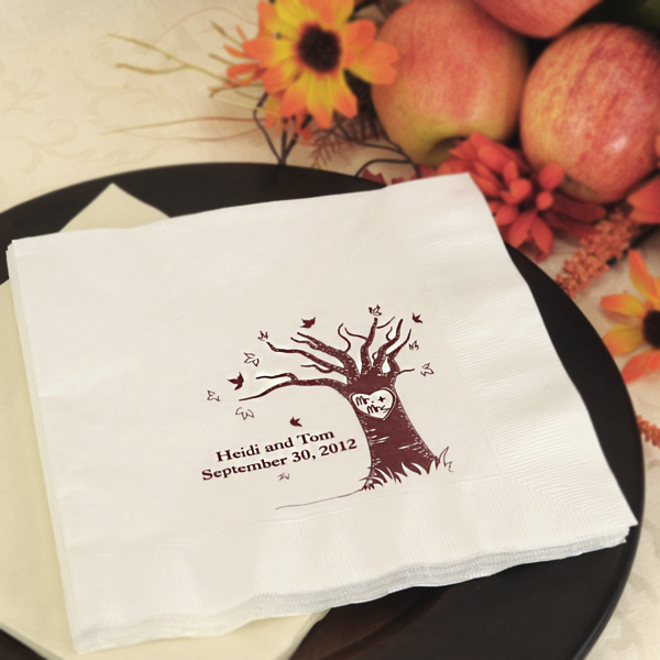 White dinner napkin printed with the Mr. + Mrs. love tree design personalized with 2 lines of custom text in wine imprint