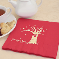 Red luncheon napkin printed with the autumn love tree design personalized with two initials printed inside a heart and stylized tree. Ivory Matte imprint color