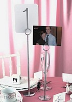 12 inch chrome stand holding photo next to 15 inch chrome stand holding table number