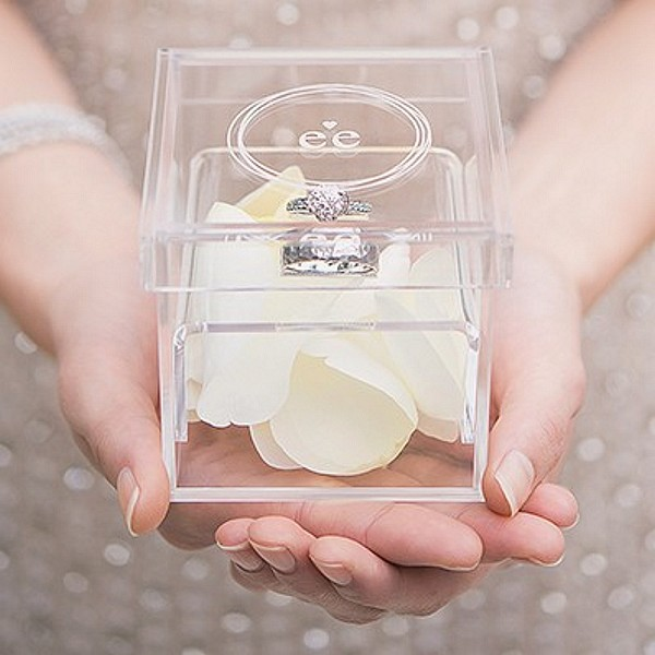 Bride holding clear acrylic his and hers wedding ring box engraved with initials and contemporary circle design