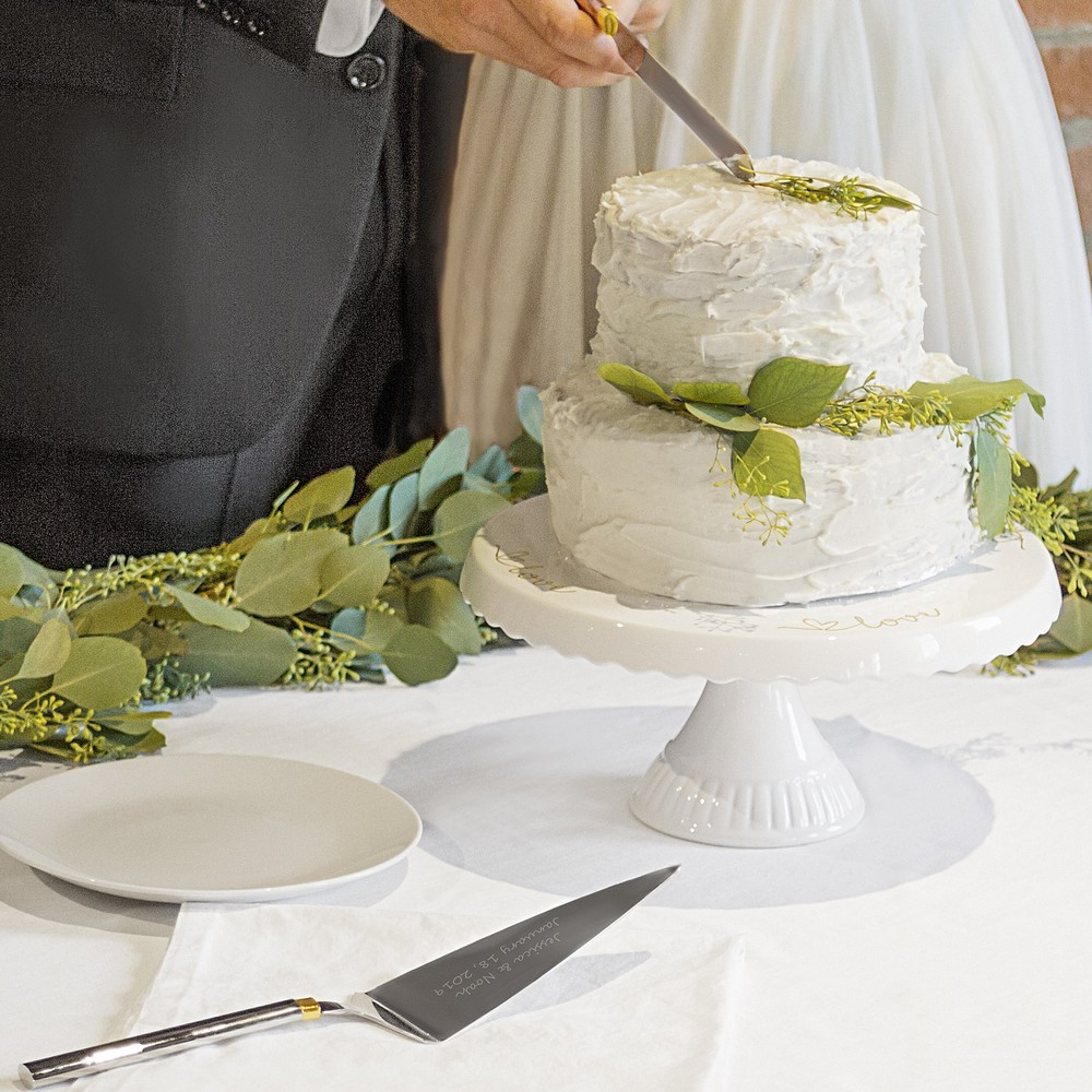 Bride and groom cutting wedding cake with personalized server set