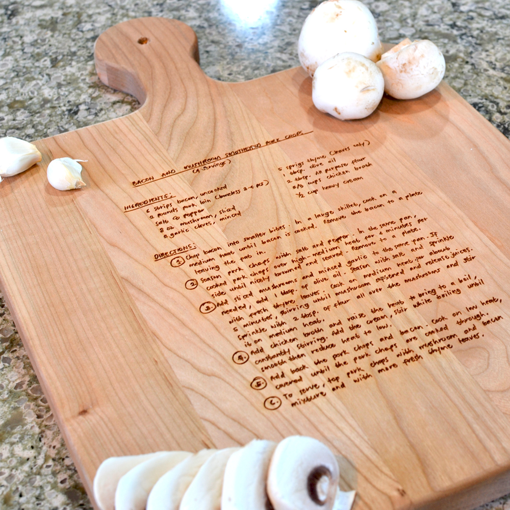 Closeup of maple cutting board, measuring 10.5x16 inches, custom engraved with a family recipe.