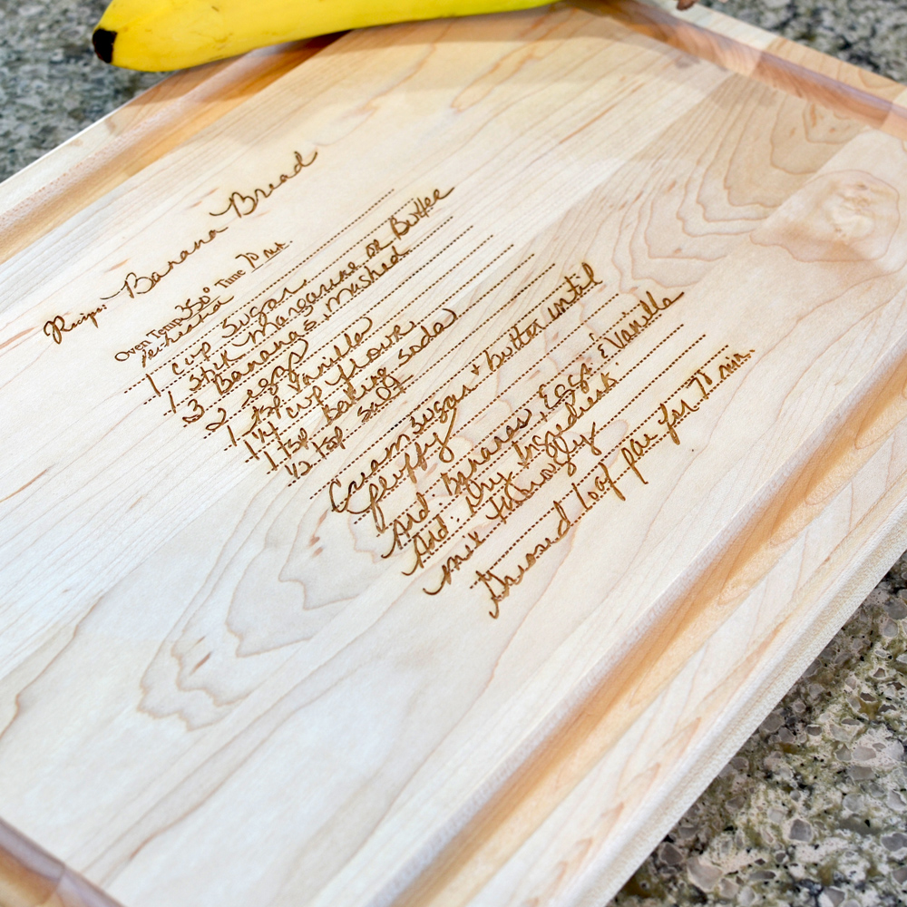 "Closeup of maple cutting board, measuring 18"" x 12"" inches, custom engraved with a family recipe."