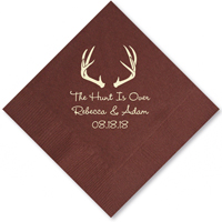 Cocktail napkin personalized with deer antlers design, 'the hunt is over' phrase, bride and groom's name and wedding date in ivory imprint color